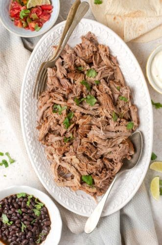 An overhead shot of instant pot pulled pork on a white platter