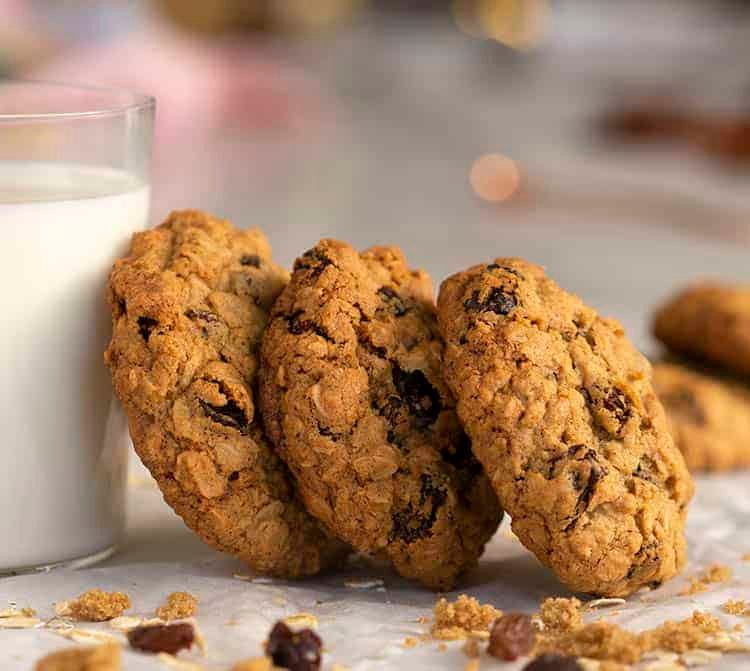 Oatmeal raisin cookies leaning a against a glass of milk.