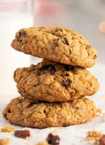 three oatmeal raisin cookies stacked next to a glass of milk