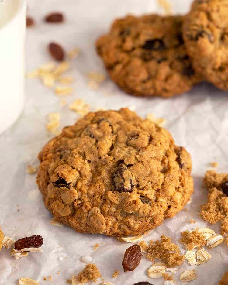 A close up of a oatmeal raisin cookie on baking parchment