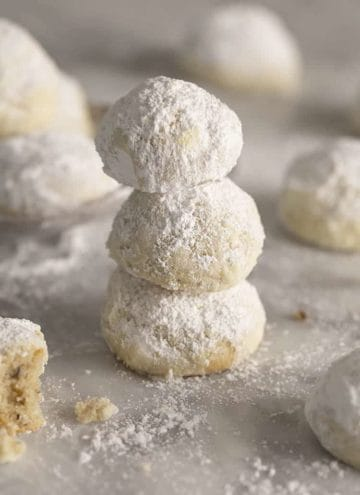 Three Russian tea cakes stacked on a marble table sprinkled with powdered sugar