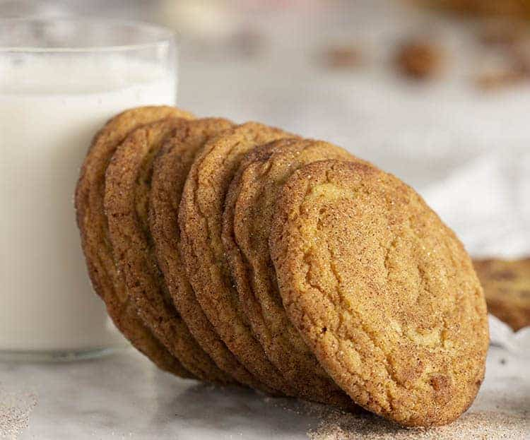 Snickerdoodle cookies next to a glass of milk.
