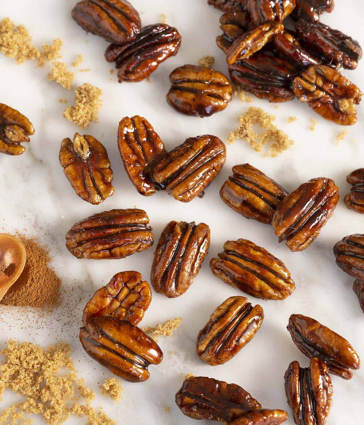 A group of candied pecans on a white marble table with cinnamon and brown sugar in frame.