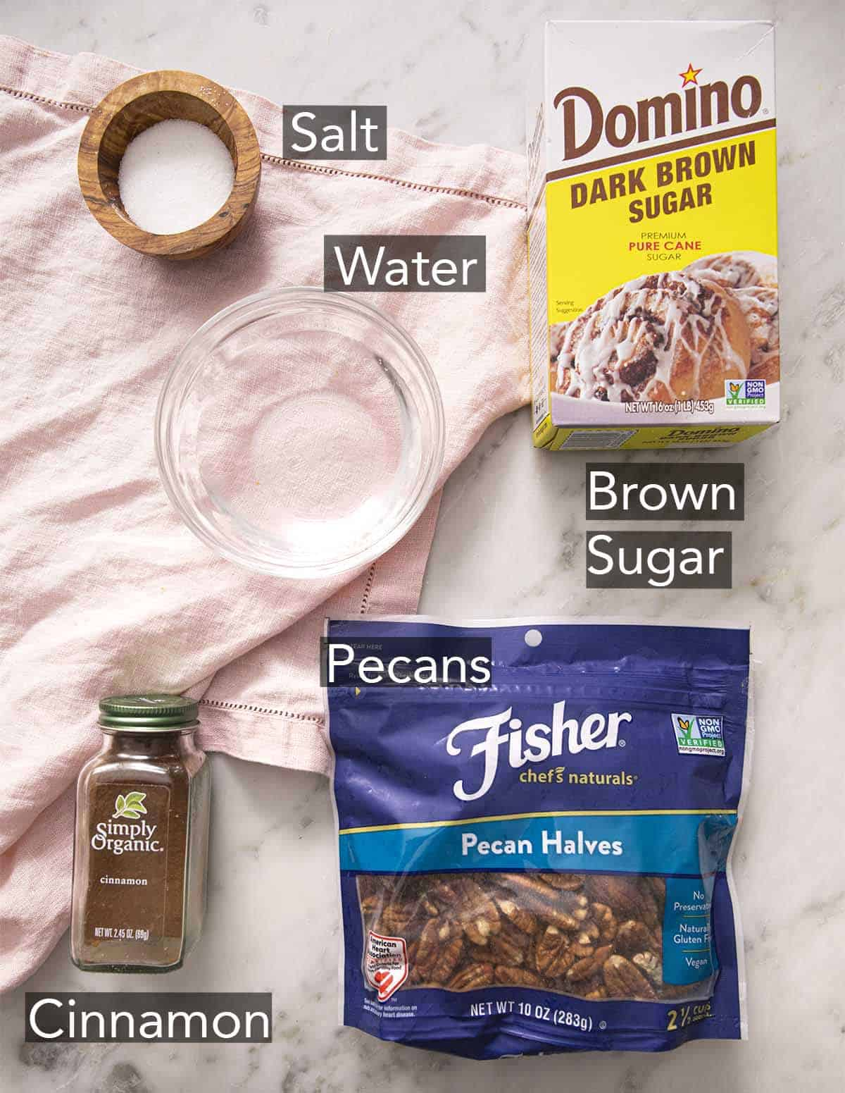 Ingredients to make candied pecans laying on a marble counter.