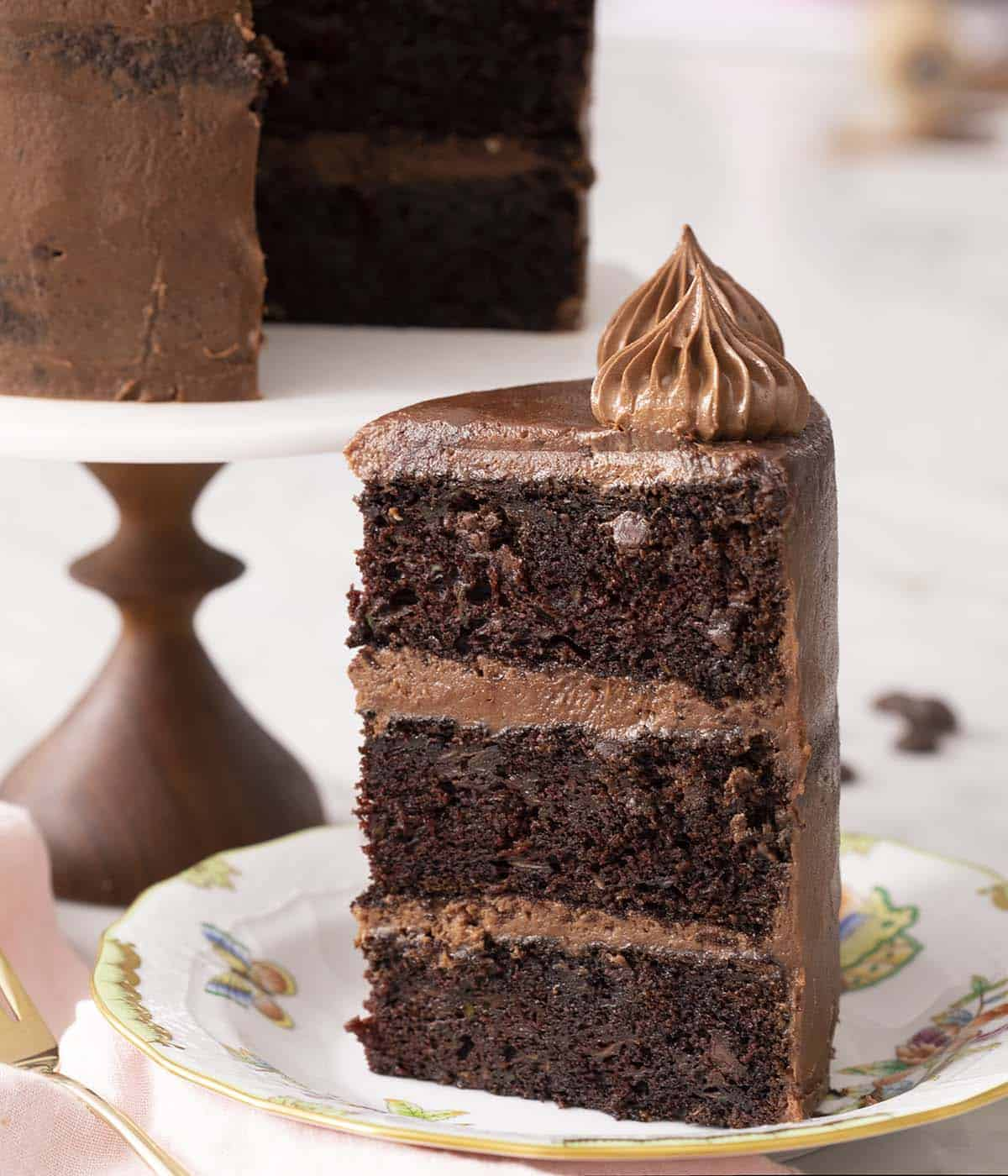 A big piece of three layer chocolate zucchini cake on a plate.