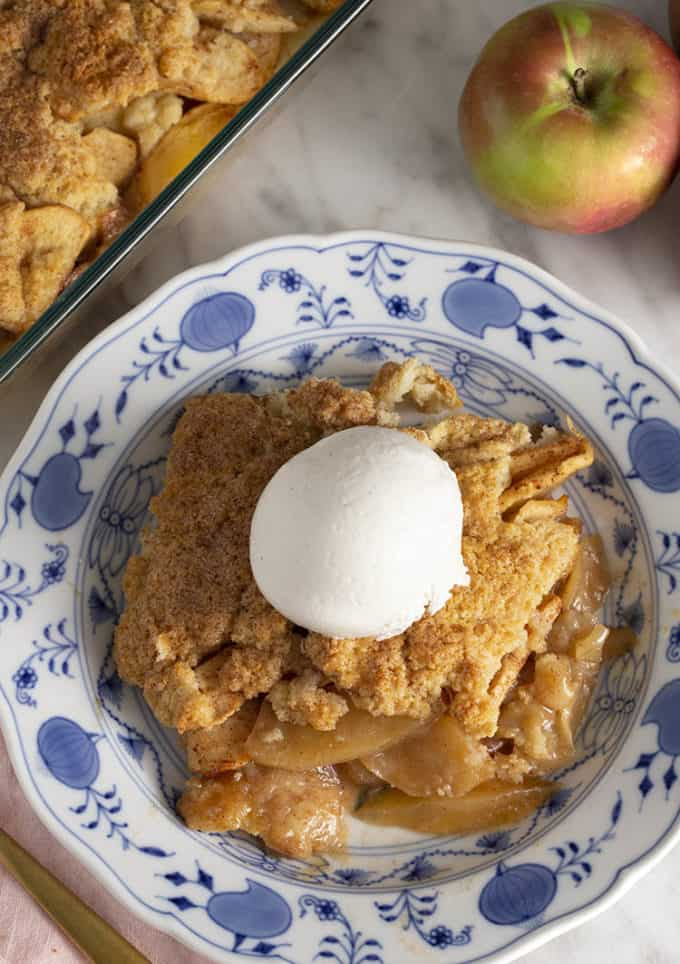 Apple cobbler on a blue and white plate next to some apples
