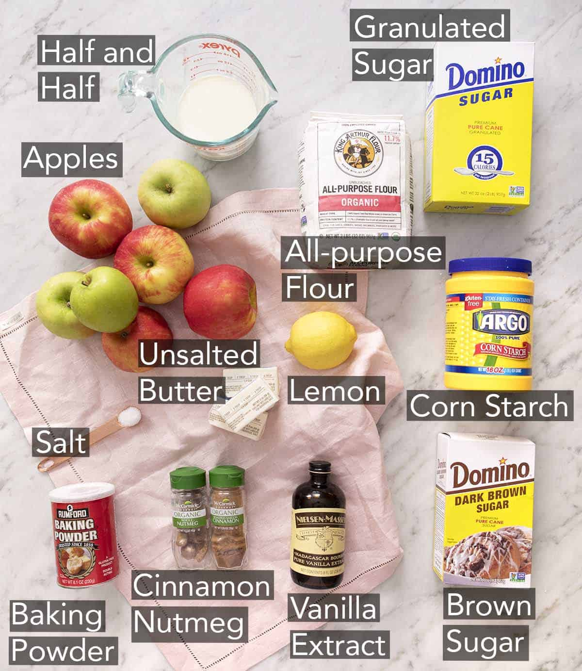 Ingredients to make apple cobbler on a marble counter.