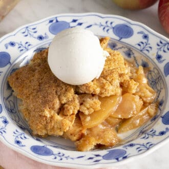 Apple cobbler on a plate with a scoop of vanilla ice cream.