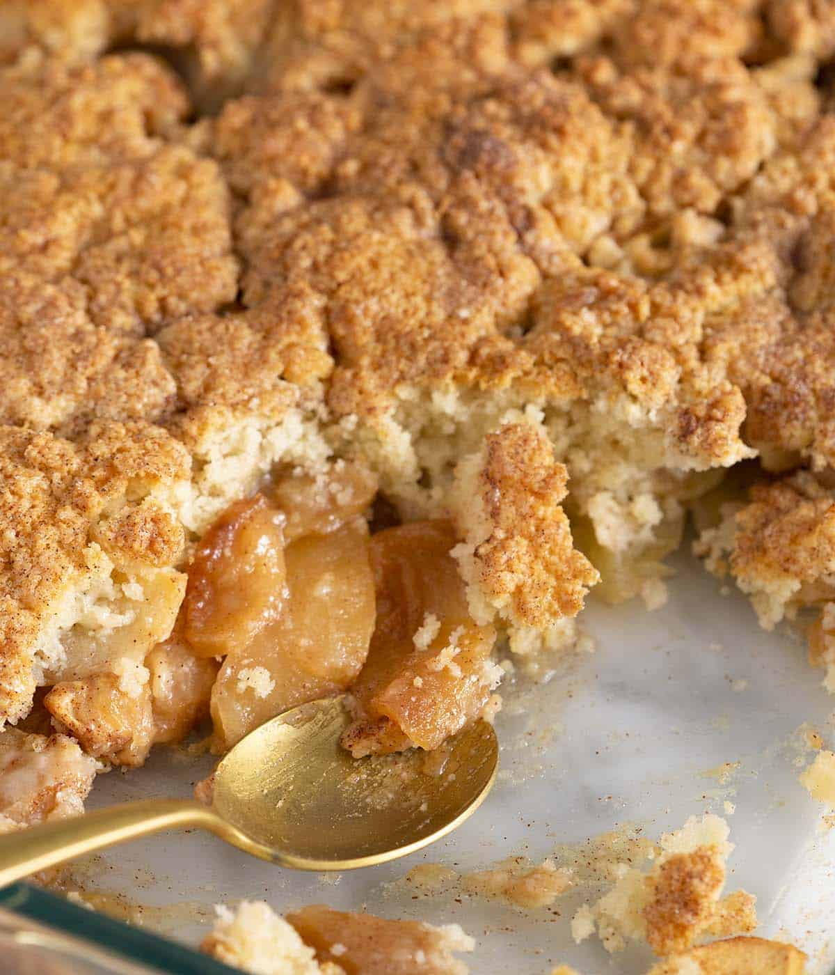 A glass dish of apple cobbler with a golden spoon.