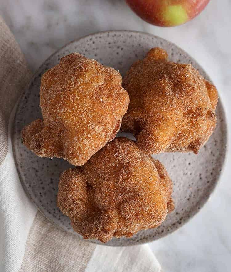 three apple fritters covered in cinnamon sugar on a grey plate