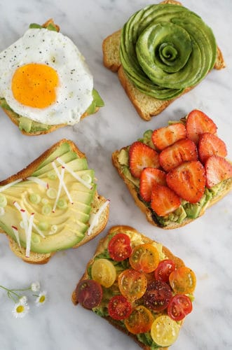 Five pieces of avocado toast on a white marble surface, each with different toppings