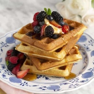 A stack of Belgian waffles topped with whipped cream, fruit and maple syrup on a blue and white plate.