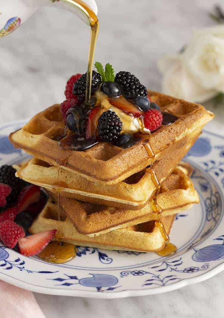 Maple syrup pouring onto a stack of Belgian waffles