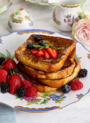 A stack of french toast with berries on a porcelain plate.