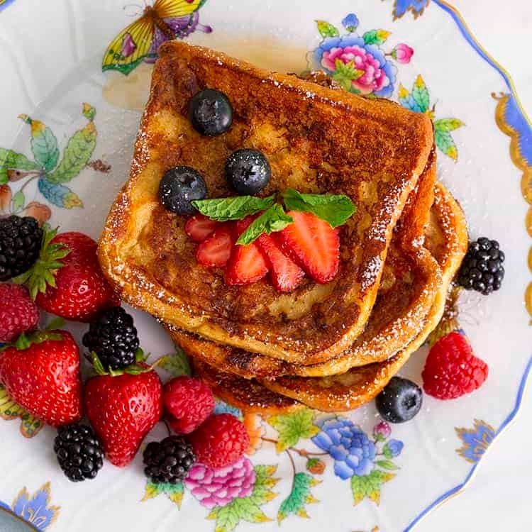 A top down view of a stack of French toast with berries on a porcelain plate.