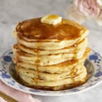 A giant stack of pancakes covered in maple syrup and butter