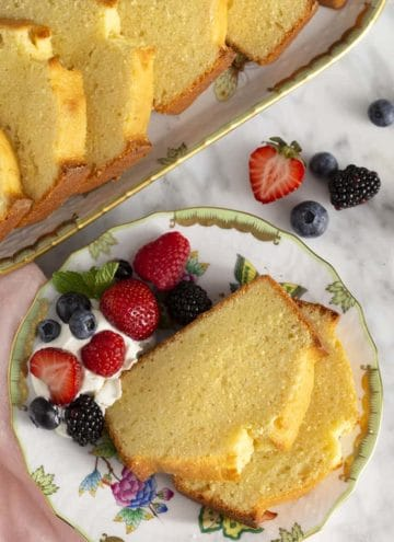 Pound cake on a plate whith whipped cream and berries