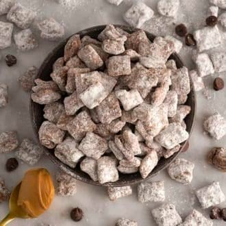 A bowl of puppy chow with chocolate chips scattered around on a marble table