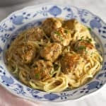 Swedish meatballs over linguini in a blue and white porcelain plate