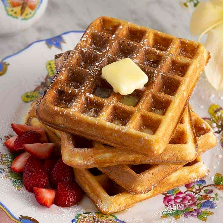 Four Waffles stacked on a plate with a pat of butter on top and strawberries as the base