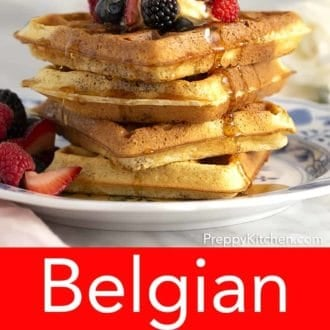 stack of belgian waffles topped with berries on a plate