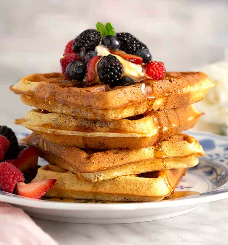 A stack of Belgian waffles topped with whipped cream and berries