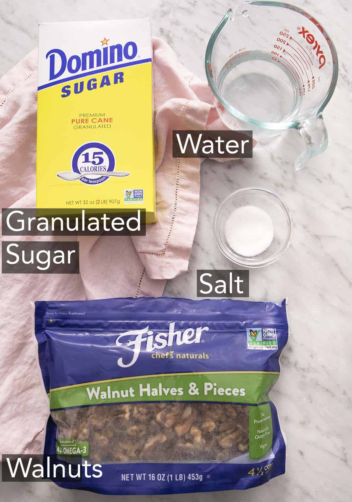 Ingredients to make candied walnuts with text labels on a marble counter.