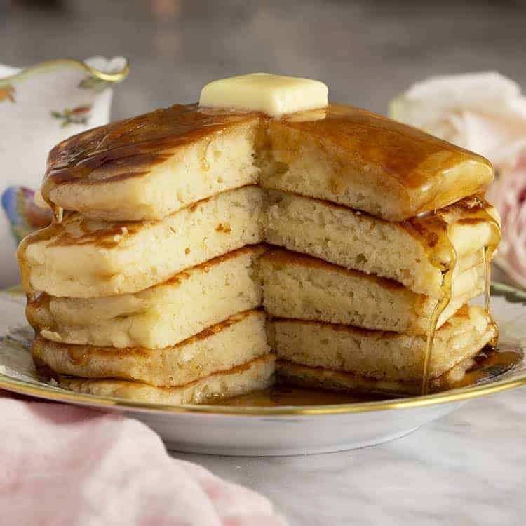 five pancakes on a place with a big piece cut out
