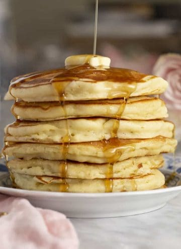 A big stack of pancakes topped with a pat of butter getting drenched in maple syrup