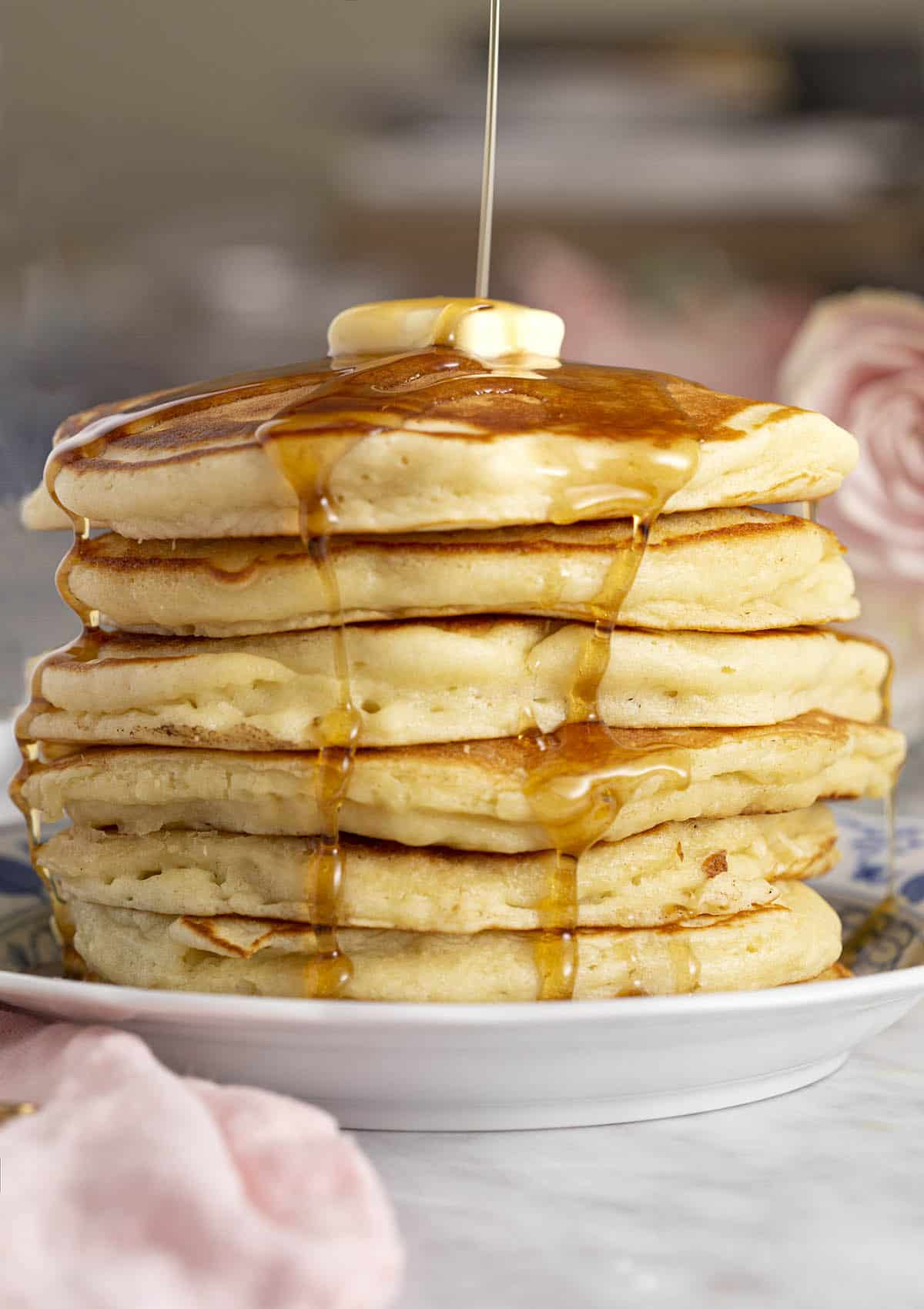 A huge stack of pancakes getting drenched with maple syrup.