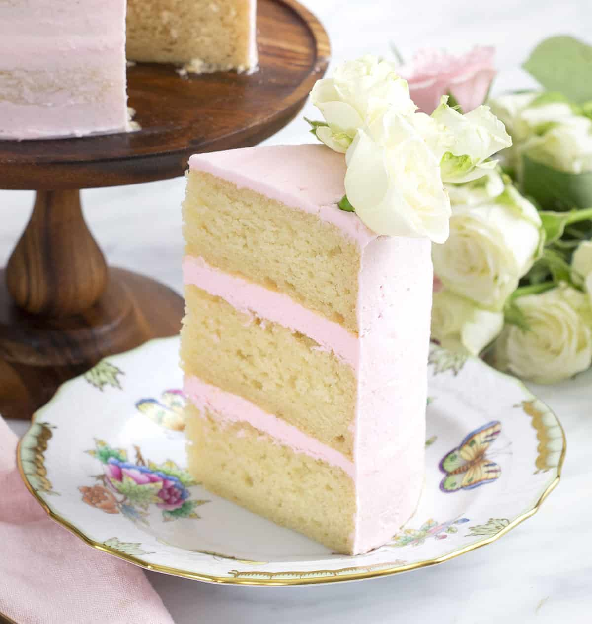 A piece of vanilla cake with light pink frosting and white roses on top.