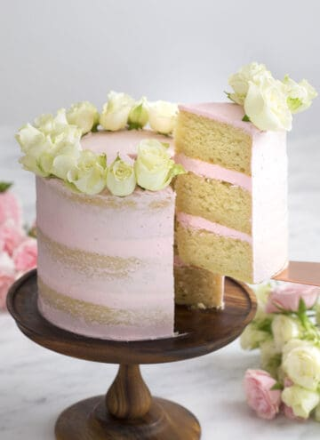 A vanilla cake with light pink buttercream an white roses on top.