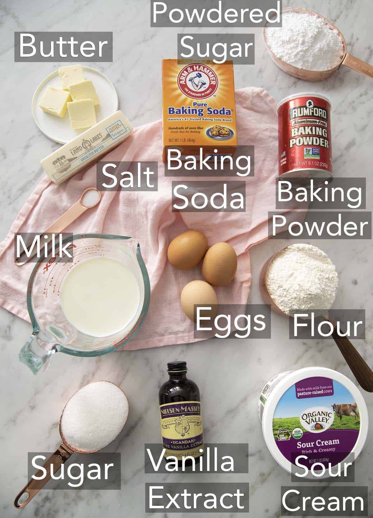 The ingredients for a vanilla cake on a marble surface.