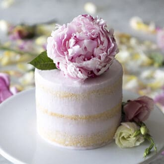 A delicious vanilla cake with three layers and a giant peony on top.