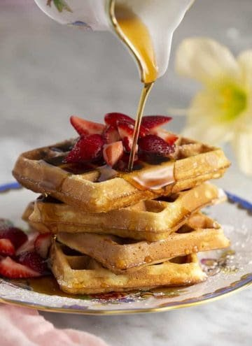A atack of waffles with strawberries on top getting a nice pour of maple syrup