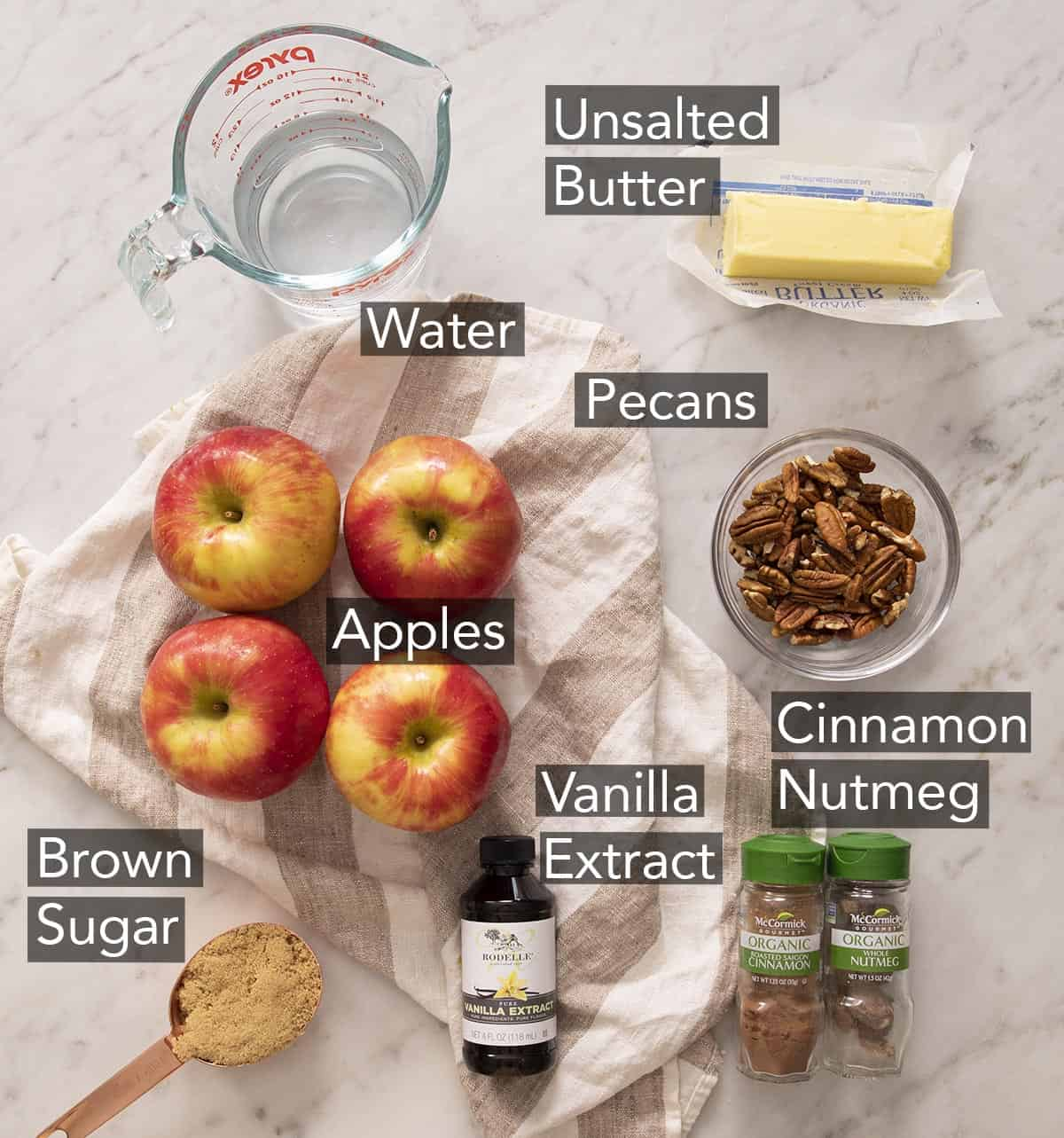 Ingredients for making baked apples on a marble counter.
