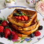 A stack of French toast on a plate topped with strawberries