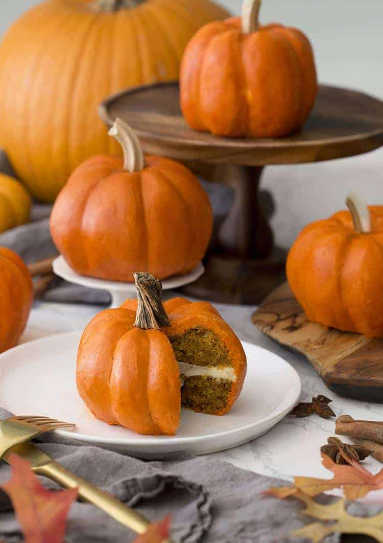 A group of small cakes that look exactly like orange pumpkins.