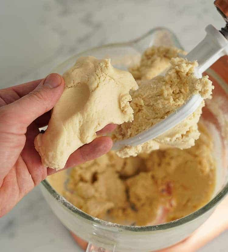 A photo of sugar cookie dough being handled
