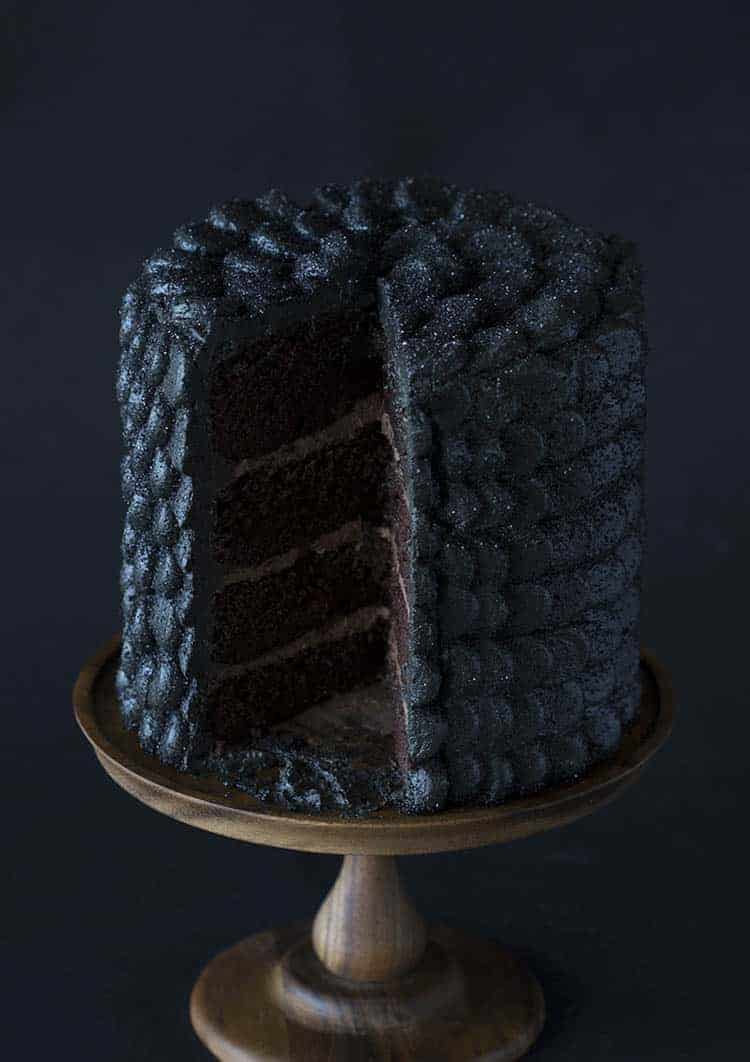 A four layer chocolate cake covered in sparkling black buttercream scales.