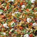 A pan of nachos loaded with toppings.