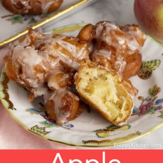 several apple fritters covered in glaze on a plate, one is torn in half.