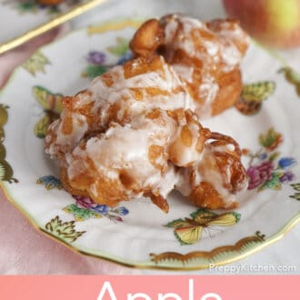 Apple fritters on a porcelain plate next to an apple.