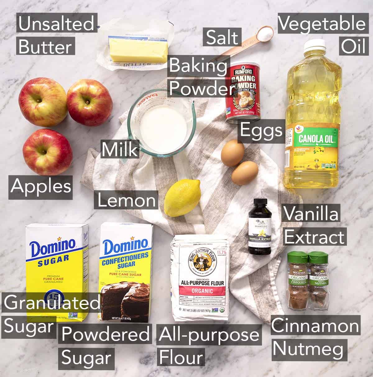 Ingredients to make apple fritters on a marble counter.