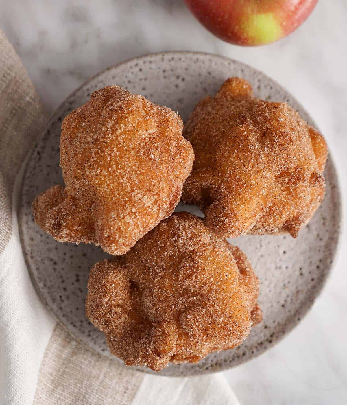 Three apple fritters covered in cinnamon sugar on a grey plate.