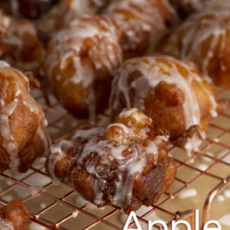 Apple fritters with glaze on a cooling rack.