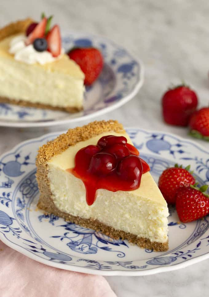 A piece of cheesecake covered with cherries on a blue and white plate.