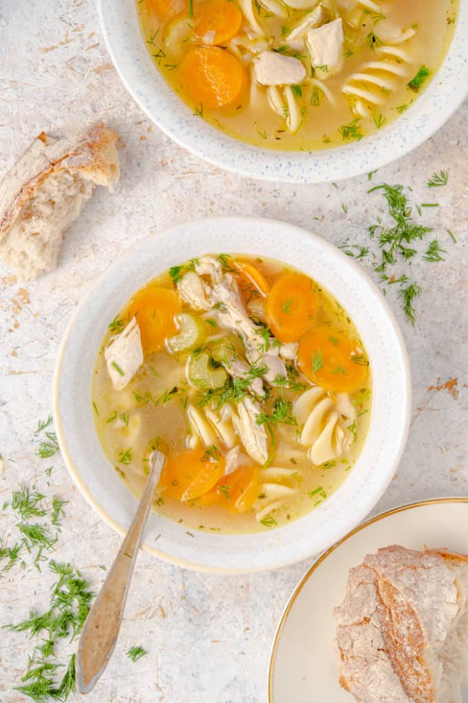 Two white bowls filled with chicken noodle soup