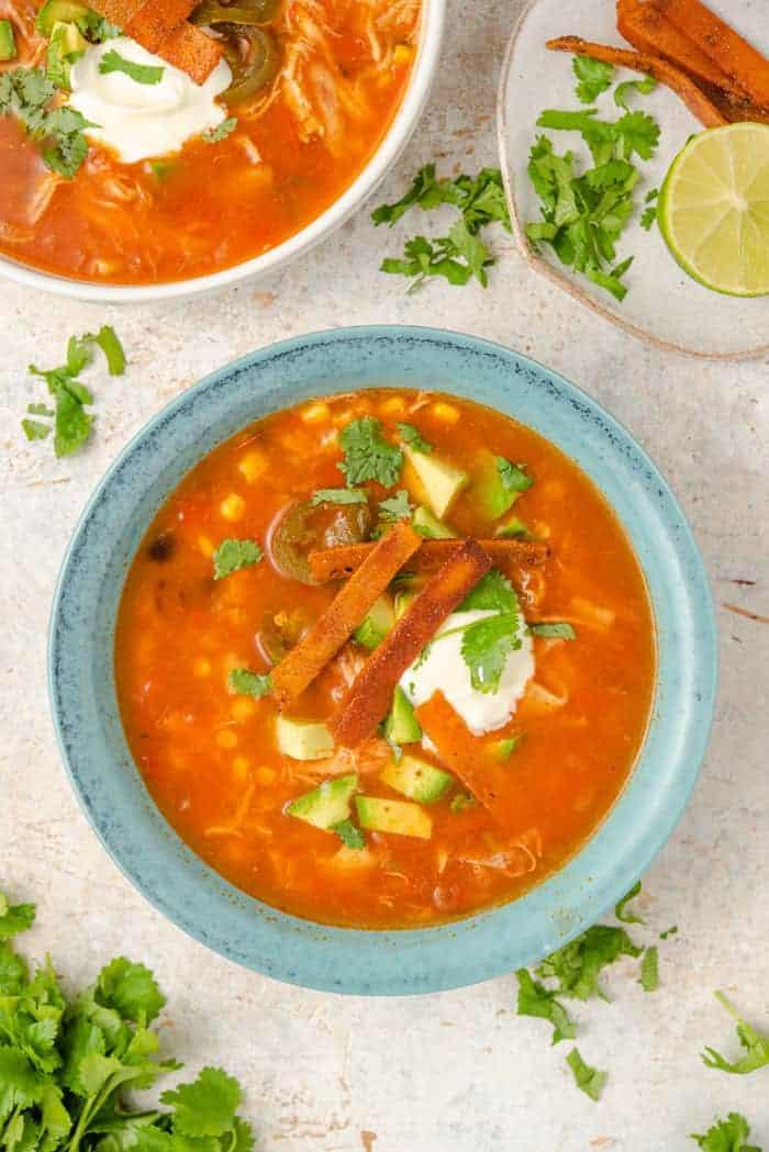 An overhead shot of chicken tortilla soup in a blue bowl
