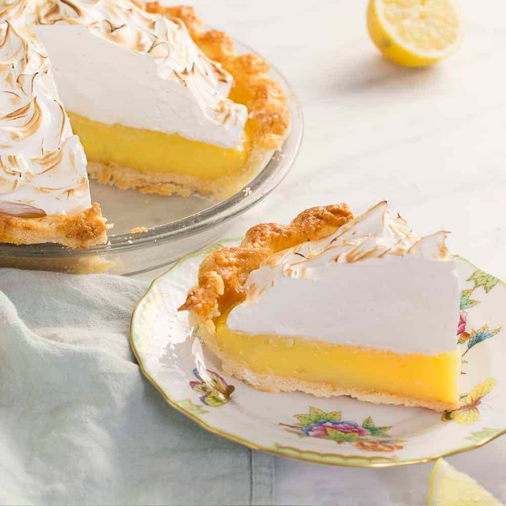 A lemon mering pie ppiece next to the cut pie on a marble table.